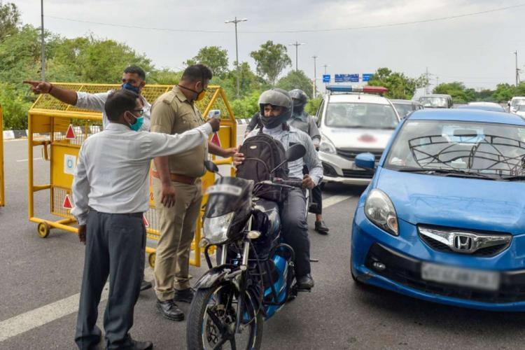 Police officials thermal screening passengers and checking the e-passes of commuters.