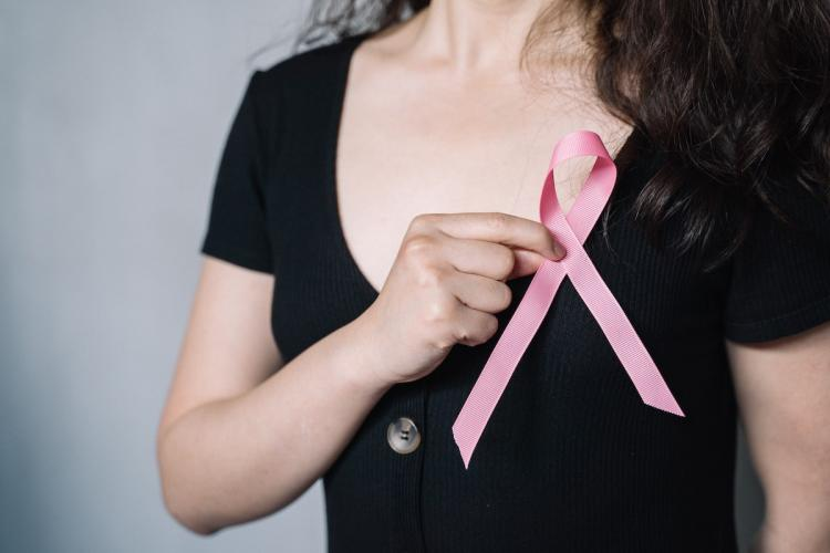 A woman wearing a black t-shirt holding a pink ribbon close to her chest an image used to represent breast cancer