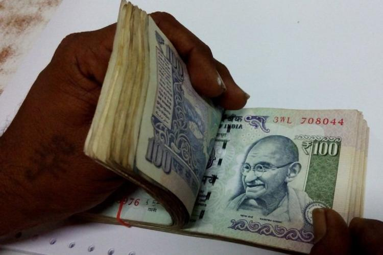 A pair of hands seen counting a wad of currency notes