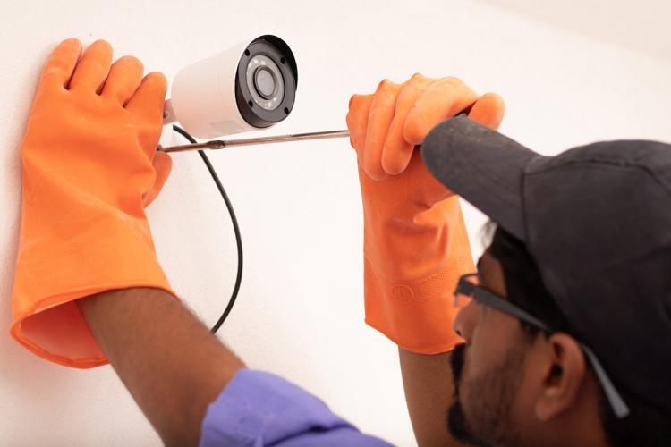 A representative image of a man fixing a CCTV camera