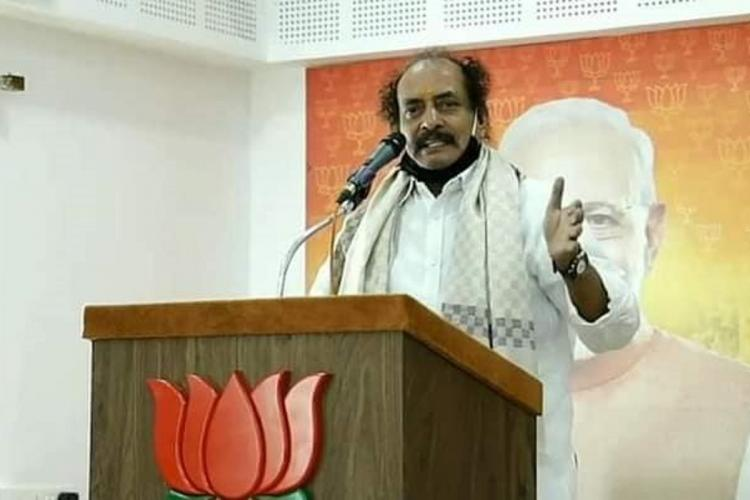 CK Padmanabhan standing before a microphone at a podium with the lotus symbol in front and Narendra Modi's picture behind him