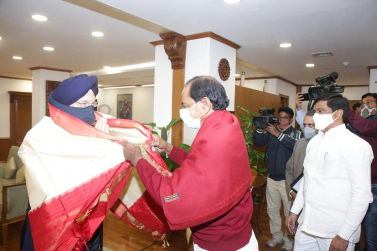 Chief Minister KCR felicitating the Aviation Minister with a shawl in his office while others take photographs