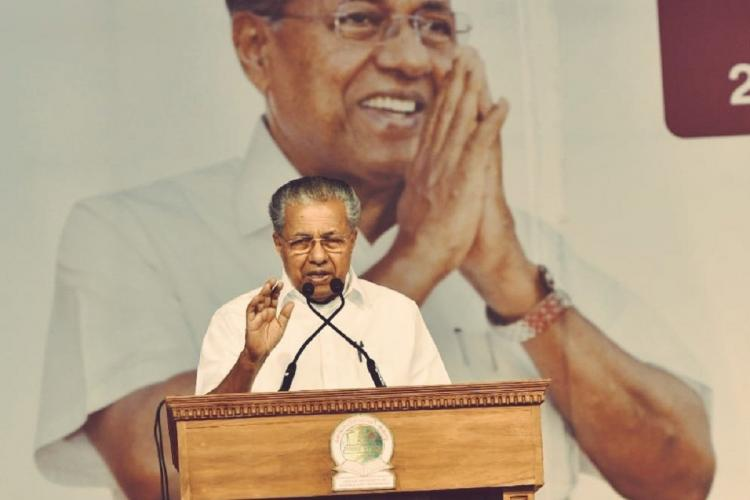 Pinarayi Vijayan at a podium, speaks, his mask under the chin, a hand raised in a gesture, and in the background is a big picture of him smiling with folded hands
