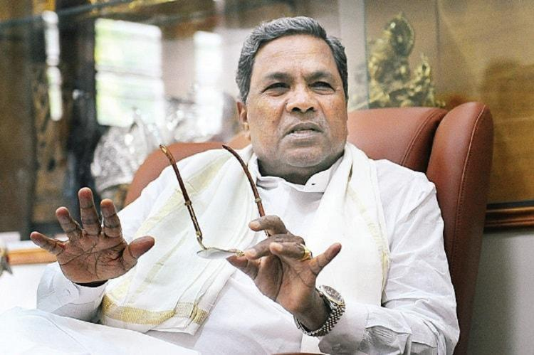 Former CM Siddaramaiah wearing a white shirt He is holding his glasses in his hand and wears an expression of disdain