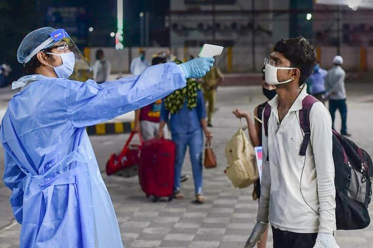Medics conduct thermal screening of passengers before boarding a train at Prayagraj