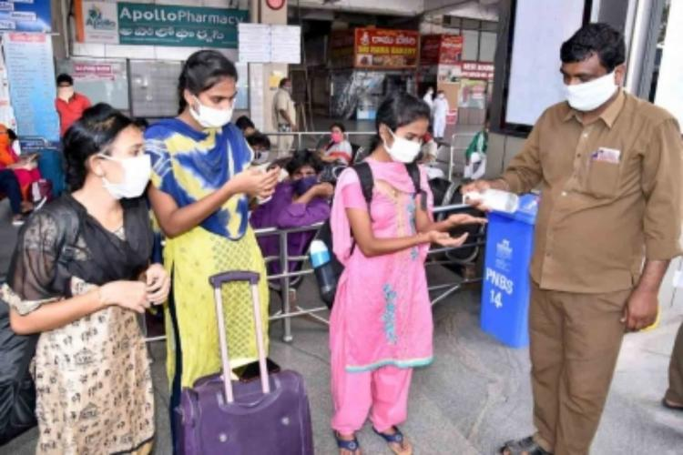 A man providing hand sanitiser at a bus stand in Andhra Pradesh