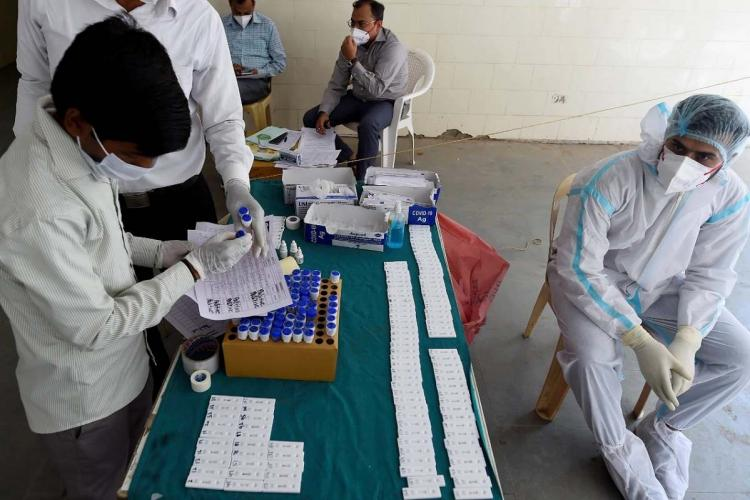 A table with COVID-19 samples, health workers sitting