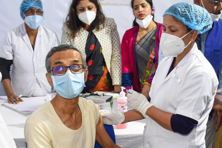 A middleaged man gets injected by a health worker and both of them are wearing surgical masks Behind them are three women also wearing masks