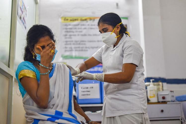 A woman wearing a nurses uniform and a mask administering COVID-19 vaccine to woman wearing saree and hiding face with right hand