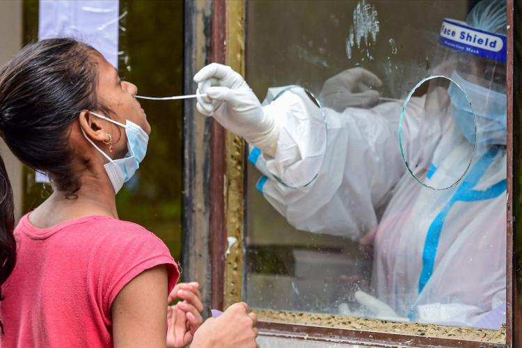 Health worker in a testing booth taking nasal swab for coronavirus test