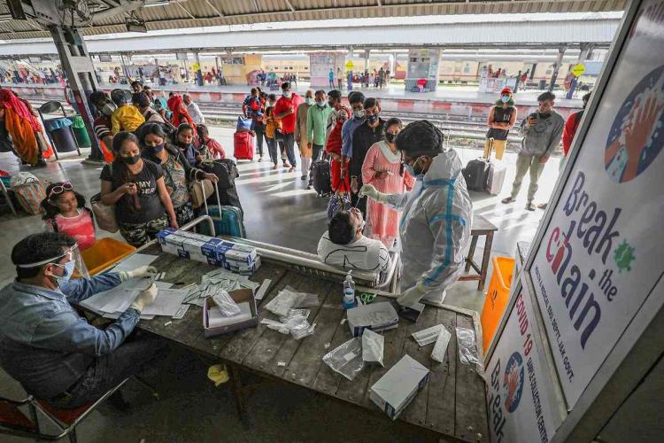 A medic takes swab samples from passengers for COVID-19 tests, at Jammu Railway station