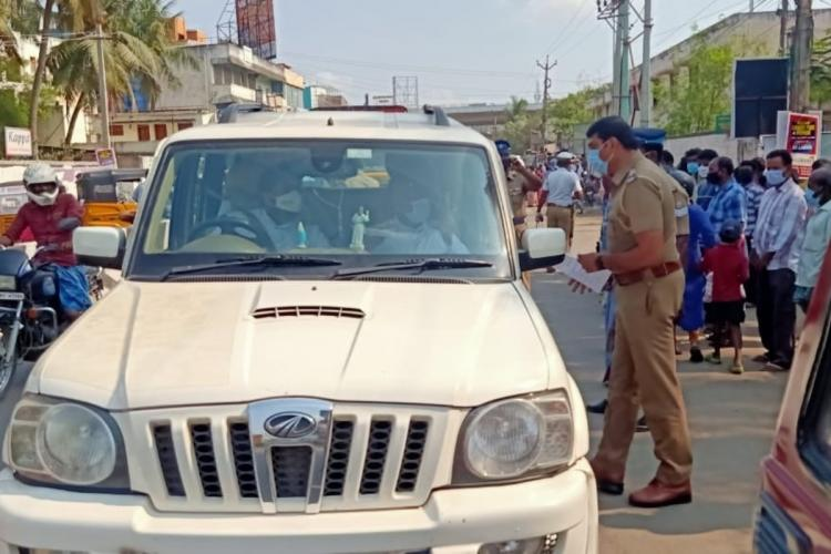 A Chennai police official talking to the passengers in the vehicle as passers-by are looking on