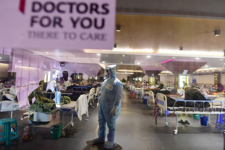 A health worker inspects COVID-19 patients undergoing treatment at Shehnai Banquet Hall converted into an isolation centre amid surge in coronavirus cases near LNJP Hospital in New Delhi