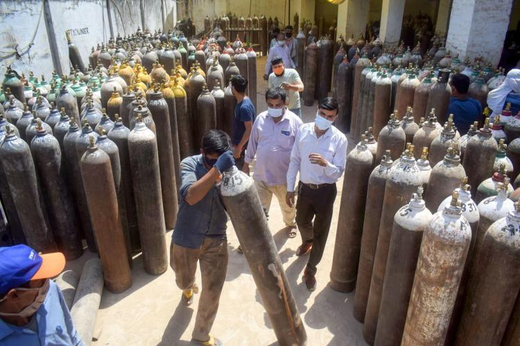A worker sorts cylinders filled with medical oxygen at a plant in Prayagraj Allahabad