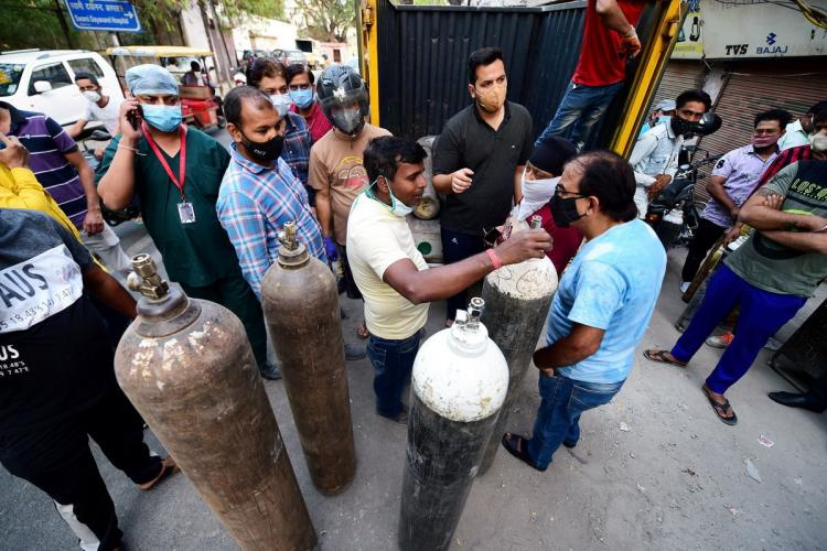 People standing around as oxygen cylinders are taken out of a truck