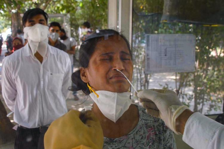 A medic collects a sample of a woman for COVID-19 test at district hospital in Noida