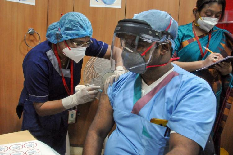 A medic administers the COVID-19 vaccine to a frontline worker, after the virtual launch of the vaccination drive by Prime Minister Narendra Modi, at AMRI-Dhakuria hospital, in Kolkata.