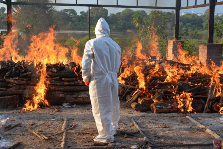 A municipal worker dressed in PPE stands before the funeral pyre of a COVID-19 victim at a crematorium