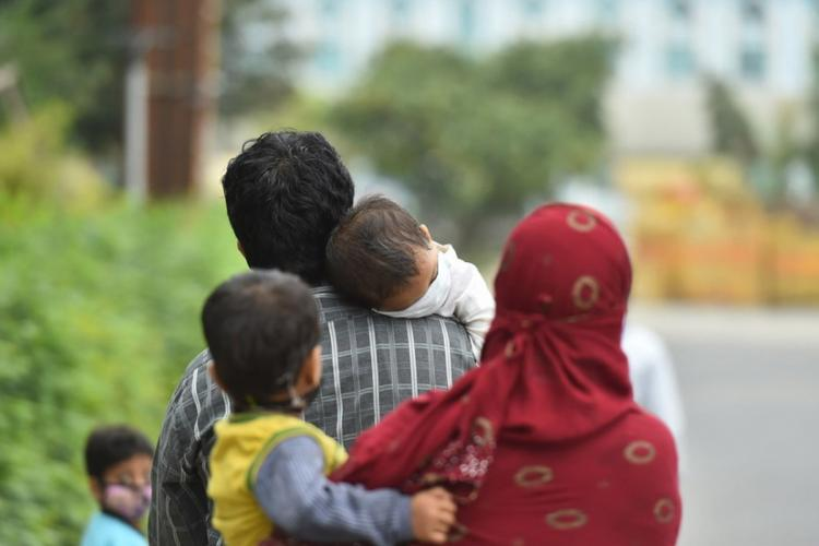 Carrying young children a couple covered with facemasks walking on a road