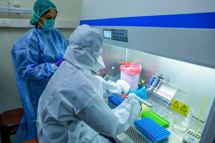 Scientists check of coronavirus variants in lab wearing PPE suits