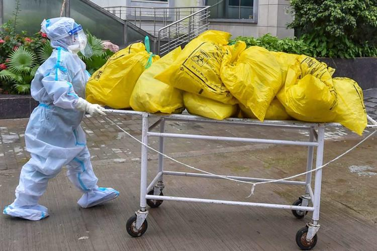 A person in PPE kit wheeling a trolley full of yellow bags