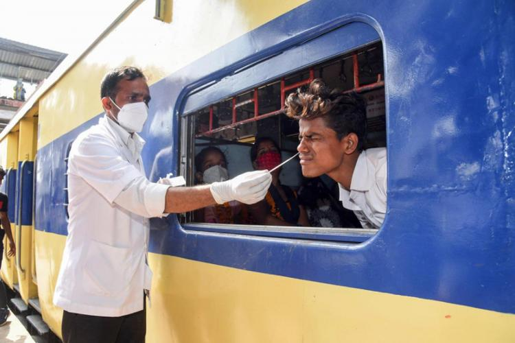A health worker takes swab sample of a passenger sitting inside a train for COVID-19 test