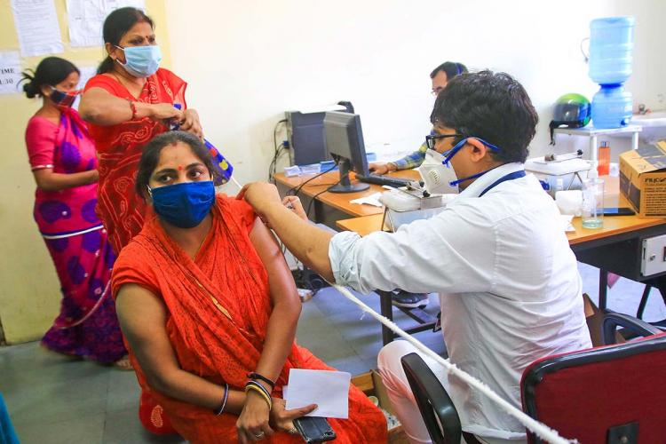 Woman wearing a mask gets COVID-19 vaccination from a health care professional as two women who are masked walk behind her
