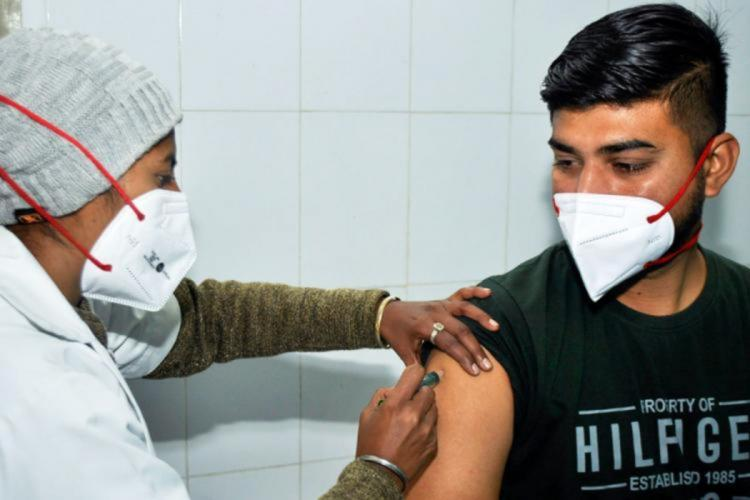 A health worker administers COVID-19 vaccine to a man in a black t-shirt Both are wearing masks