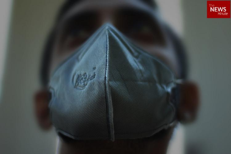 A close up photo of a person taken from below. He is wearing a mask