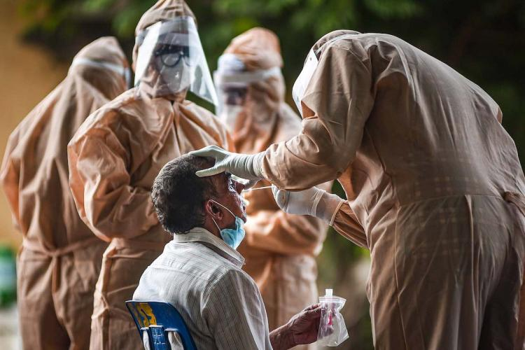 Frontline workers in full PPE kits conduct a test on a patient amid the coronavirus pandemic