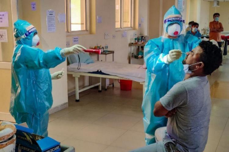 A health worker wearing PPE suit mask and gloves collecting nasal swab from a man for coronavirus test