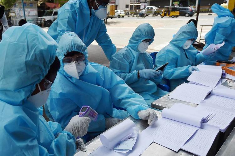 Corporation workers in PPE suit sitting to check lists and enrol people With facemasks and infra red thermometers they are poring over papers and reports