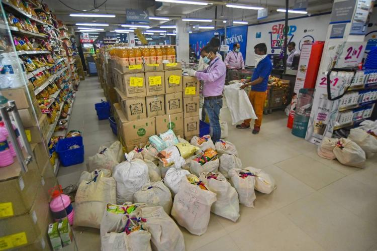 Workers of a grocery store prepare packets for home delivery during nationwide COVID lockdown in Prayagraj