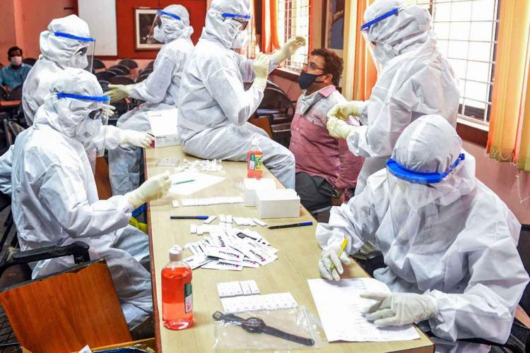 A number of health workers sit on either side of a table in PPE kits working on papers and taking testing samples