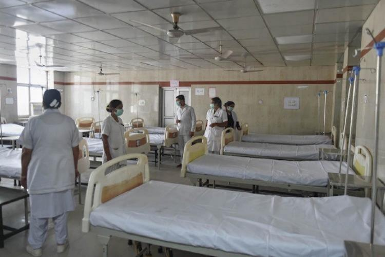 Beds and nursing staff in hospital