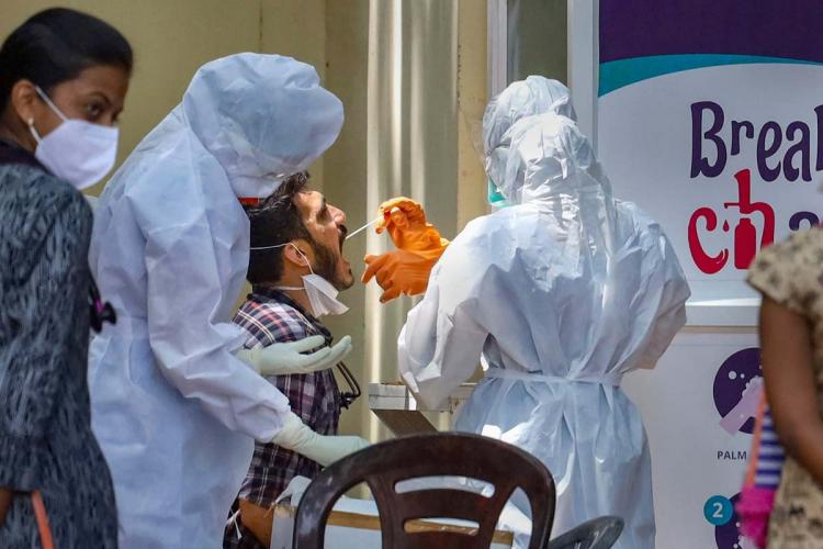 Health workers in PPE collecting swab from a man