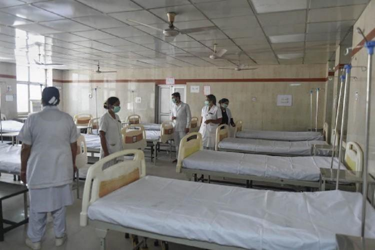Five nurses standing around empty hospital beds in a ward all in white uniform