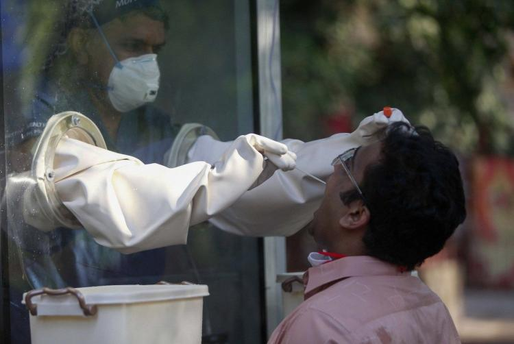Man giving his swab sample to a healthcare worker in India