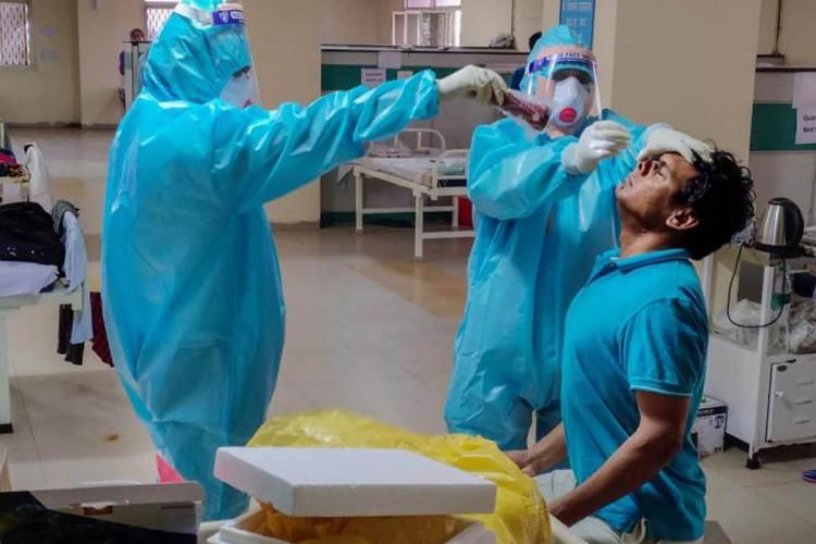 Two people in blue PPE suits take swab of man for COVID-19 testing