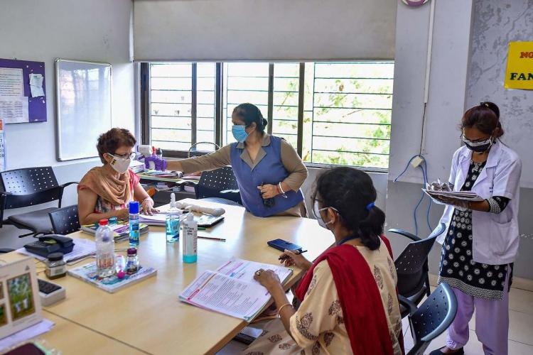 Women faculty members being screened for body temperature for COVID-19