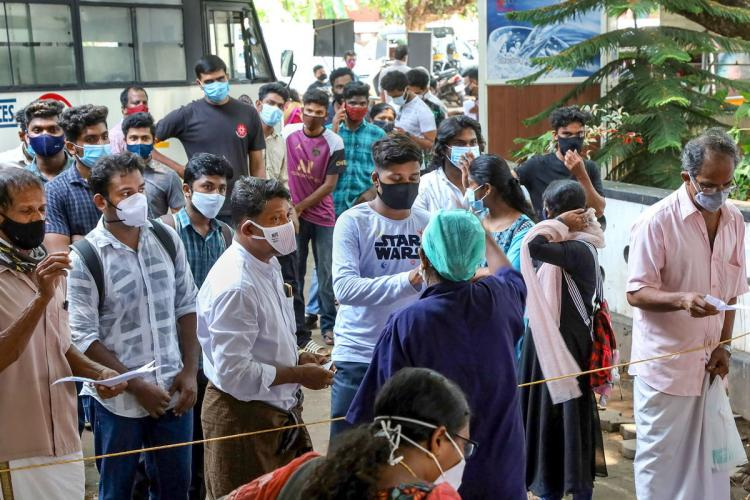 People wait to undergo COVID-19 tests as coronavirus cases surge in Kozhikode