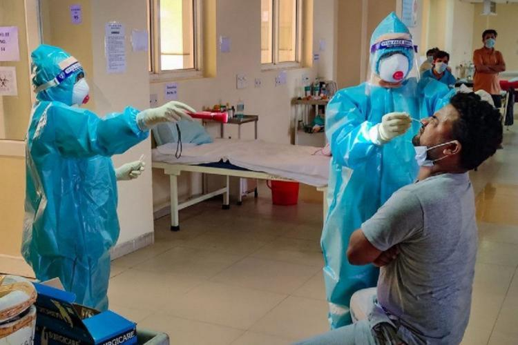 Health workers in PPE kit taking COVID test