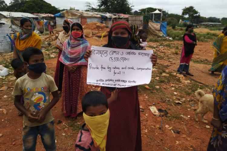 Women standing with children carrying placards