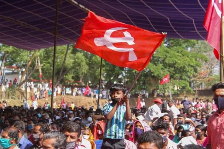 A child waves a CPI(M) red flag above him as he stands in he middle of a crowd