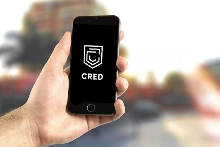 A phone held up with the Cred logo on it