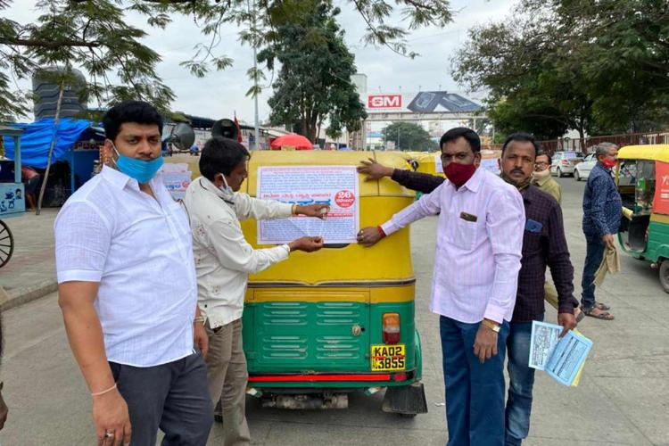 Cab and auto drivers pasting pamphlets on vehicle supporting the strike