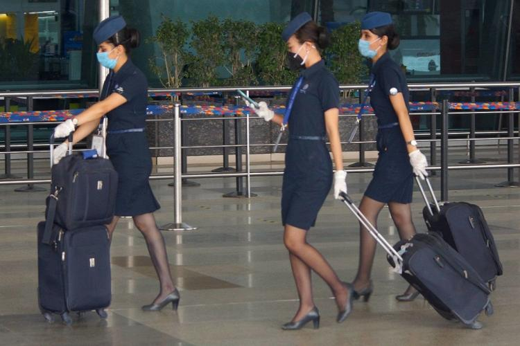 Cabin crew of an airlines wearing mask and walking