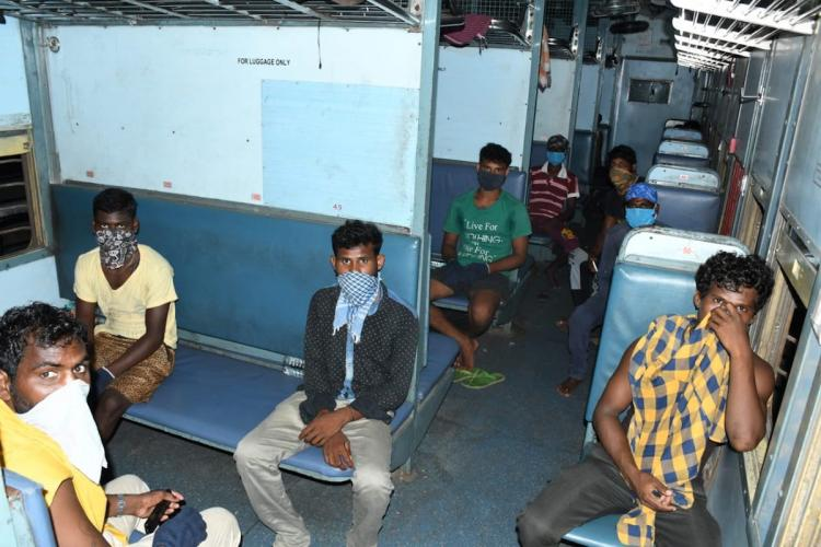 Migrant workers inside train compartment seated following social distancing rules