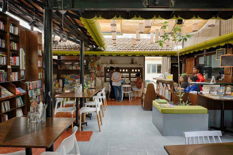 Interiors of a bookstore and cafe. Shelves of books on one side, with tables next to it.