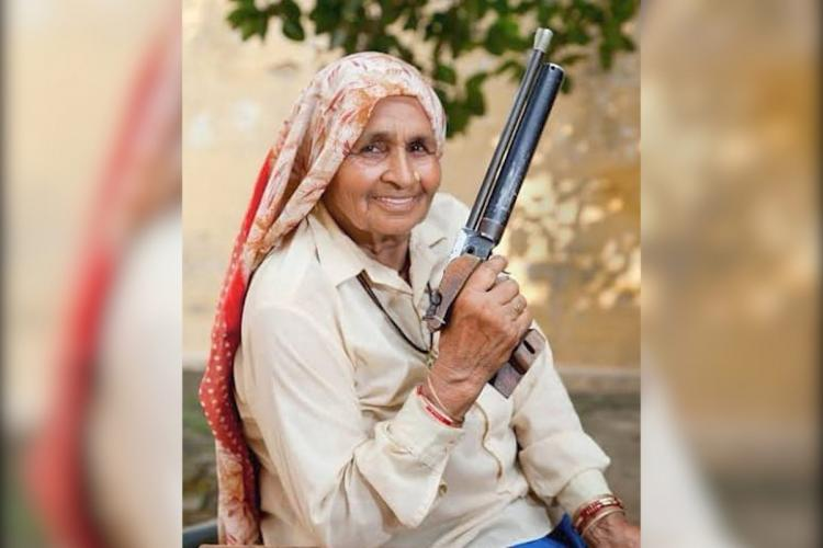 Chandro Tomar in a cream coloured shirt holding a pistol in her right hand